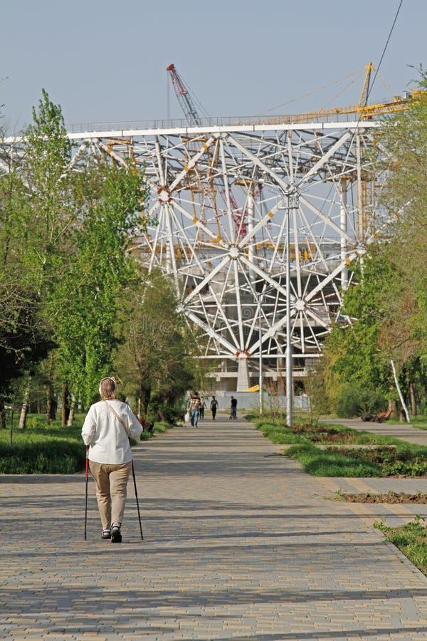 步行在一新的橄榄球场`伏尔加格勒竞技场`的背景建筑的公园的资深妇女世界杯的在20 免版税图库摄影