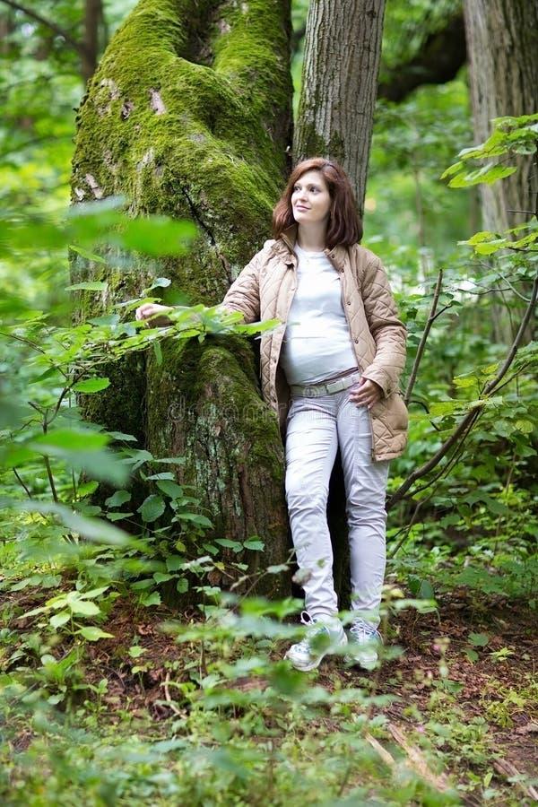步行在公园的年轻美丽的孕妇 免版税库存照片