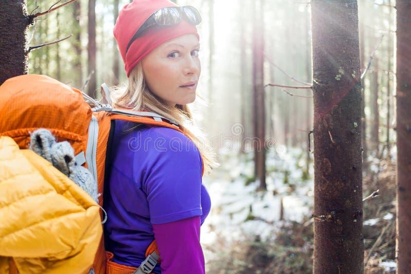 步行在冬天森林阳光下的妇女 免版税库存照片