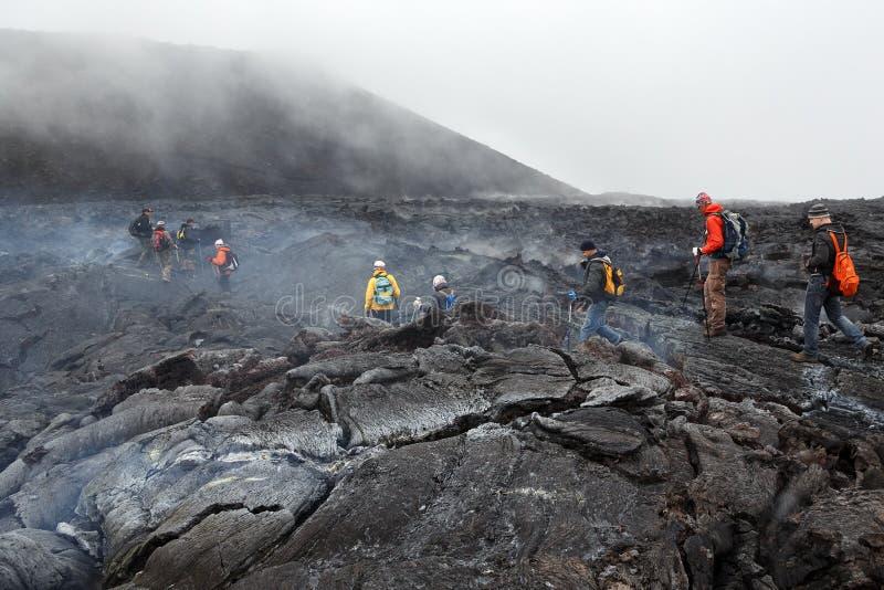 步行在堪察加的热和通入蒸汽的熔岩荒野爆发扎尔巴奇克火山火山的游人 俄国 免版税库存图片