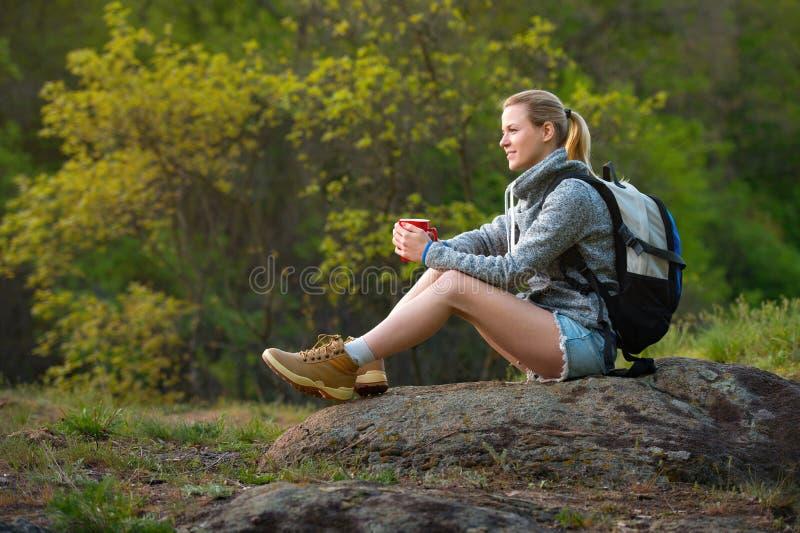 步行在夏天森林里的妇女背包徒步旅行者和停下来有res 免版税库存照片