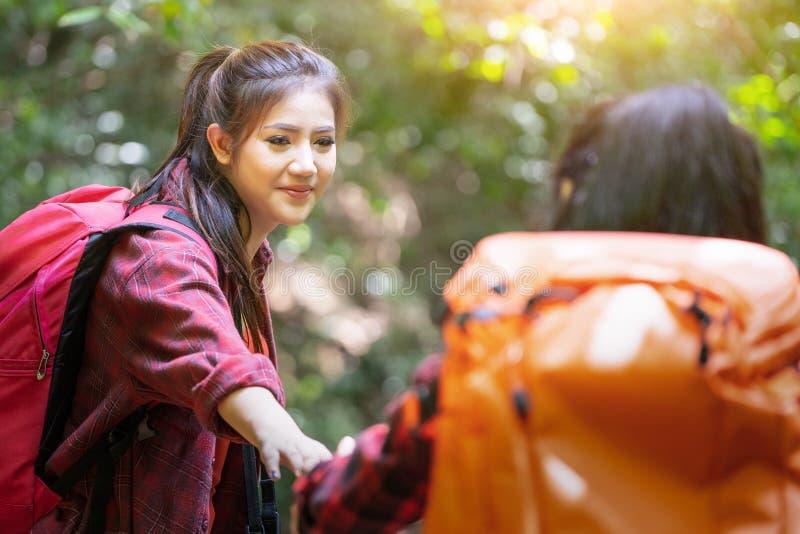 步行在山假日狂放的冒险的亚裔夫妇行家秋天森林公园,帮助,帮助,企业成功和队wor 库存图片