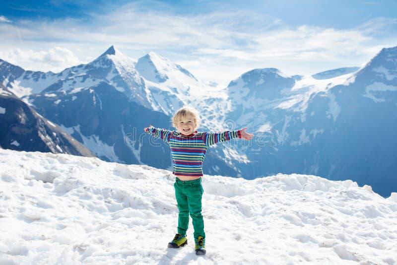 步行在山的孩子 在雪的孩子在春天 库存图片