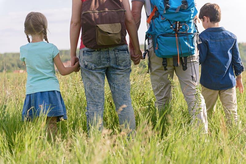 步行在山的年轻家庭 免版税库存照片