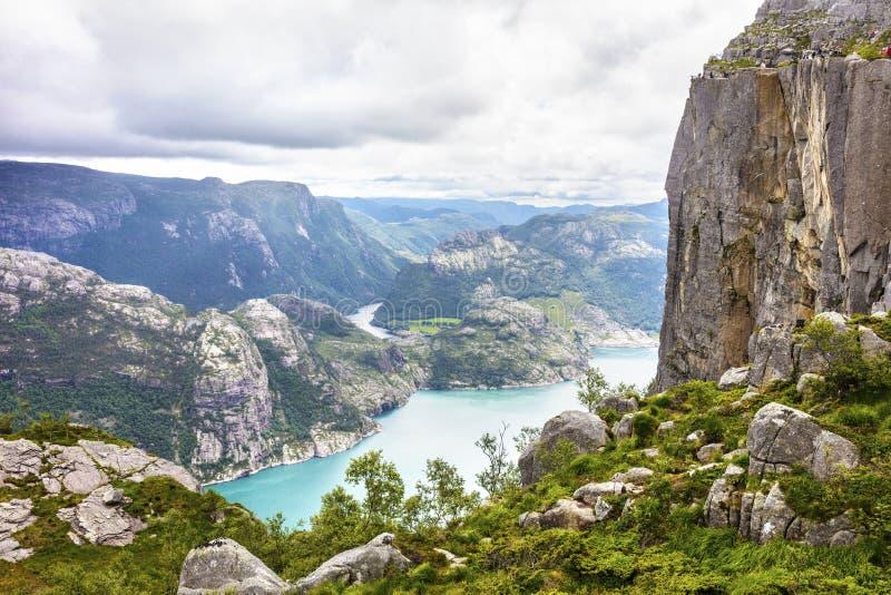 步行在布道台峭壁的游人lysefjorden挪威 免版税库存图片