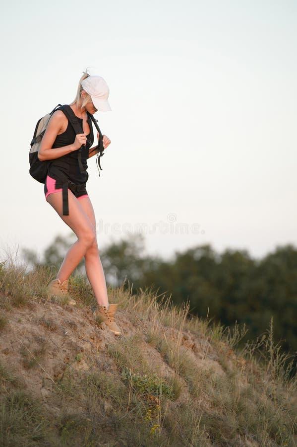步行在春天森林足迹的少妇远足者 库存照片
