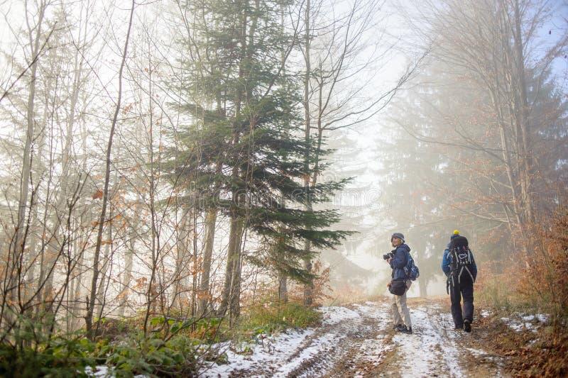 步行在有雾的森林山行迹的男人和妇女背包徒步旅行者 免版税库存图片