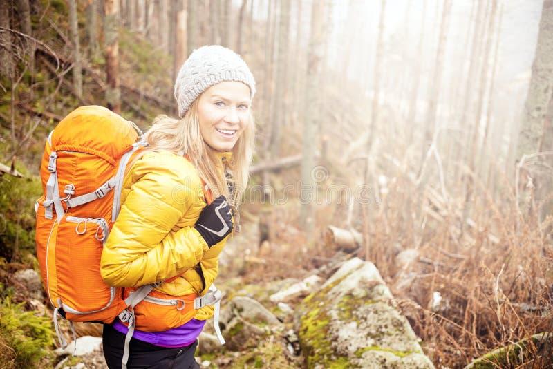 步行在秋天森林足迹的妇女 免版税库存图片