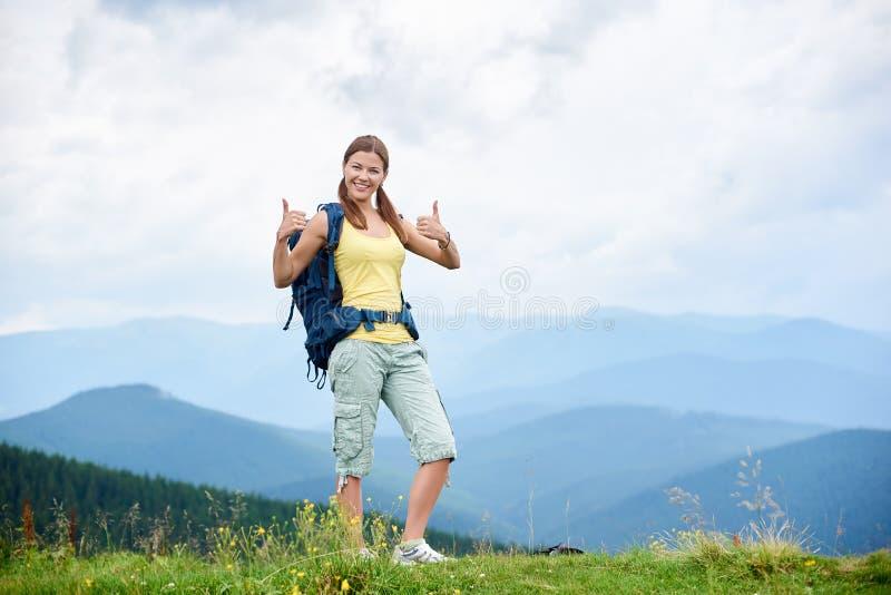 步行在象草的小山,佩带的背包的妇女徒步旅行者,使用在山的迁徙的棍子 库存照片