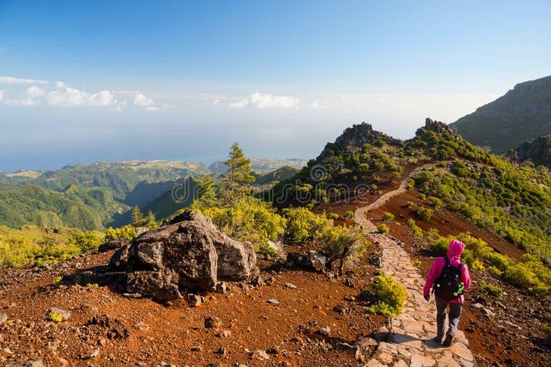 步行在道路的少妇对Pico Ruivo,马德拉岛海岛,葡萄牙高山  库存照片