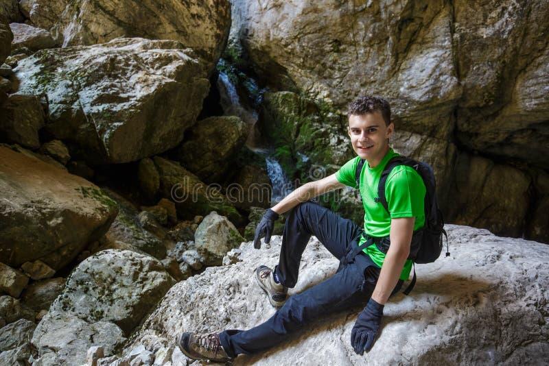 步行在洞的瀑布附近的愉快的少年 免版税库存图片