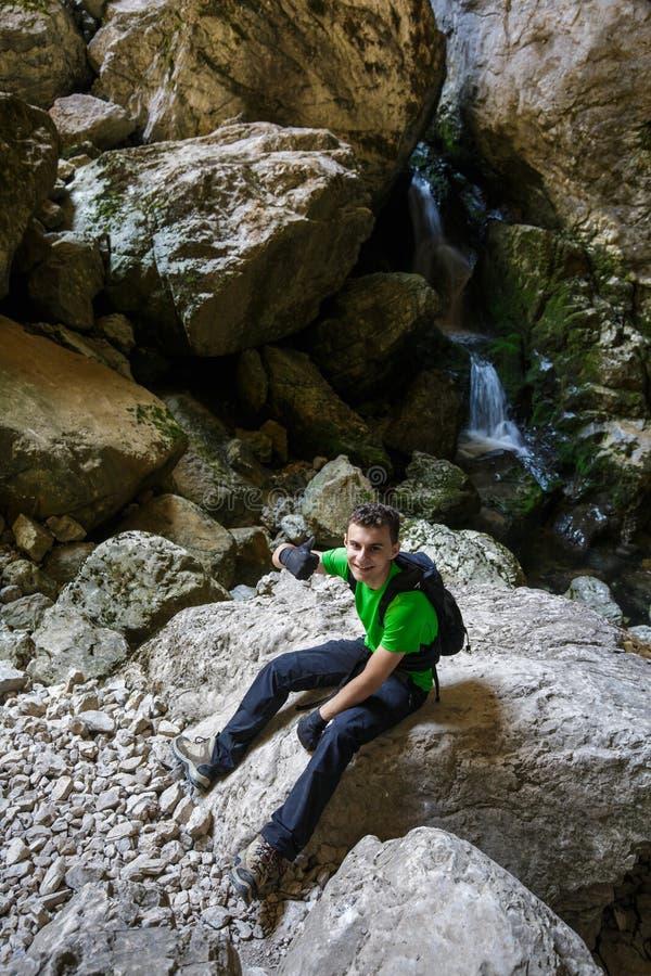步行在洞的瀑布附近的愉快的少年 图库摄影