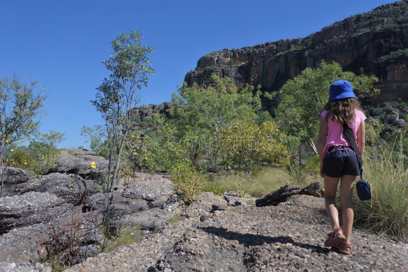 步行在Burrungkuy Nourlangie岩石艺术站点的少女在澳大利亚的卡卡杜国家公园北方领土 免版税库存照片