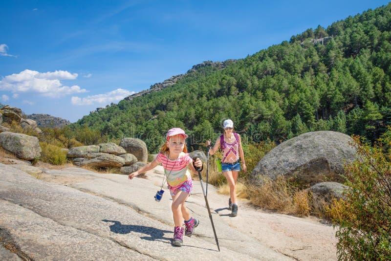 步行在Camorza峡谷的登山家妇女和小孩在马德里附近 库存照片