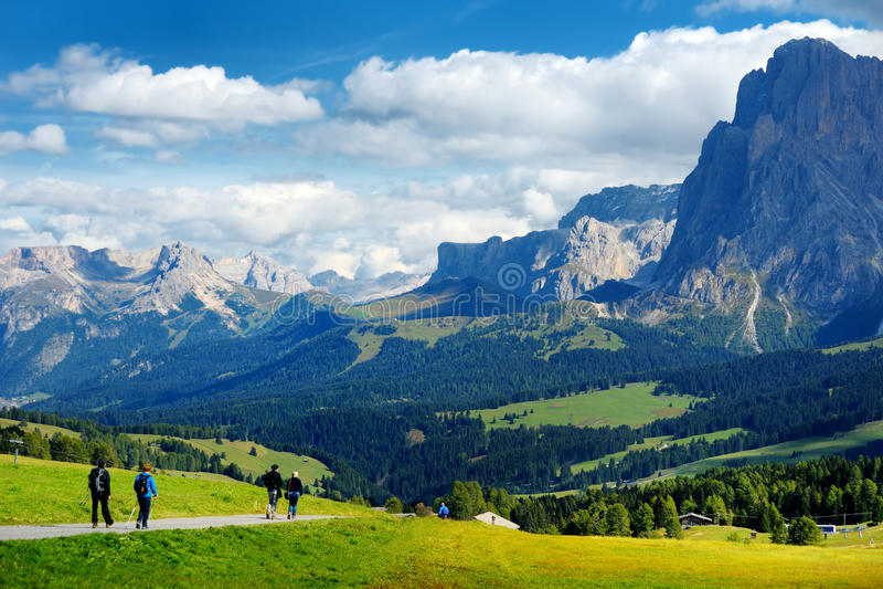 步行在Seiser Alm,最大的高处高山草甸的游人在欧洲,在背景的惊人落矶山脉 图库摄影