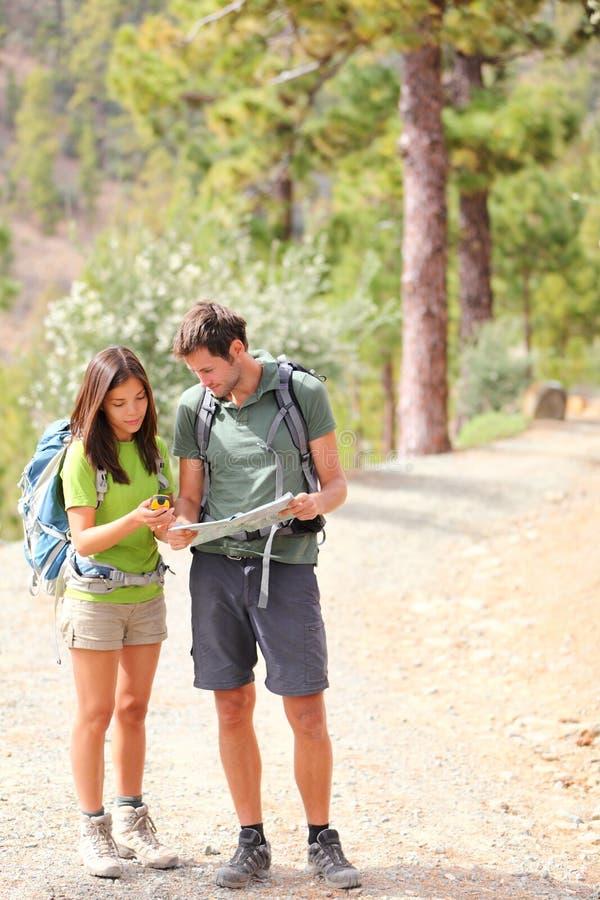 步行夫妇的远足者查找映射 库存照片