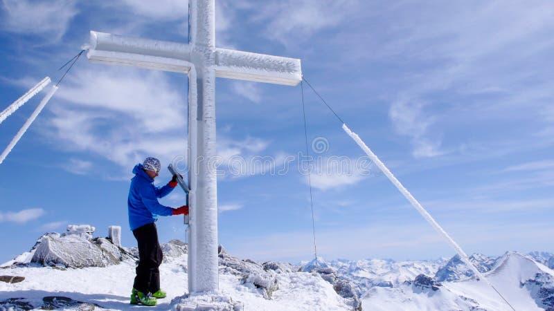 步行对一个高高山山顶的男性backcountry滑雪者在沿一个岩石和雪土坎的瑞士在轻的雾 免版税库存照片