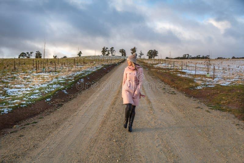 步行沿着向下一条乡下公路的妇女在冬天 免版税图库摄影