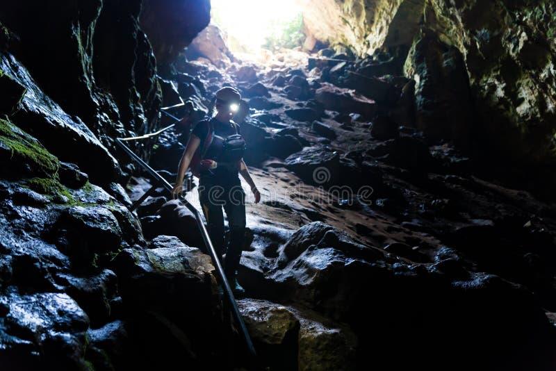 步行沿着向下与车灯的石洞的妇女 库存图片
