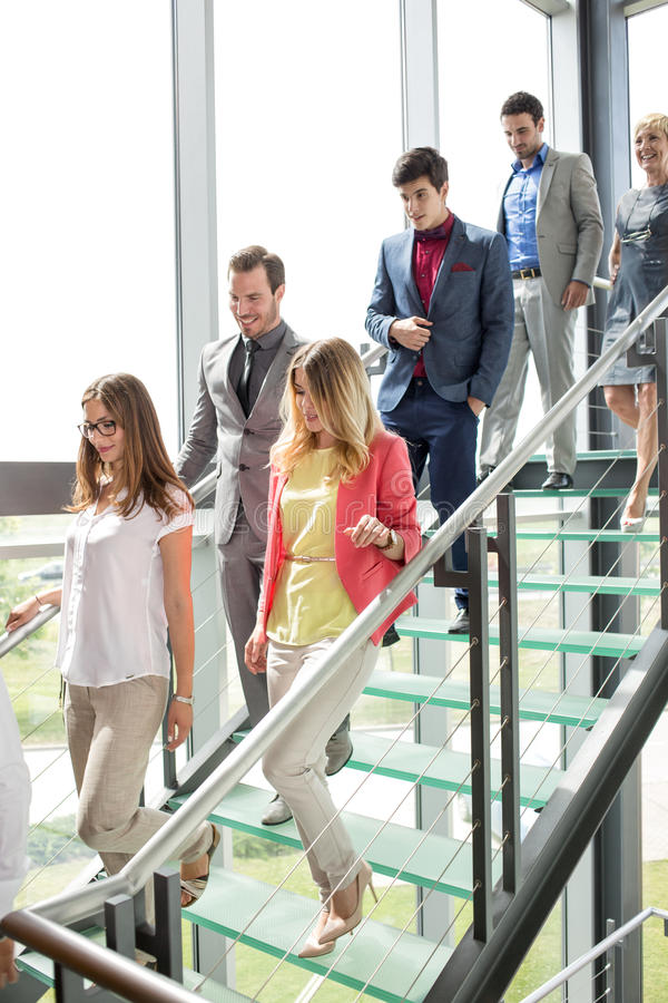 步行沿着向下台阶的微笑的商人 免版税库存照片