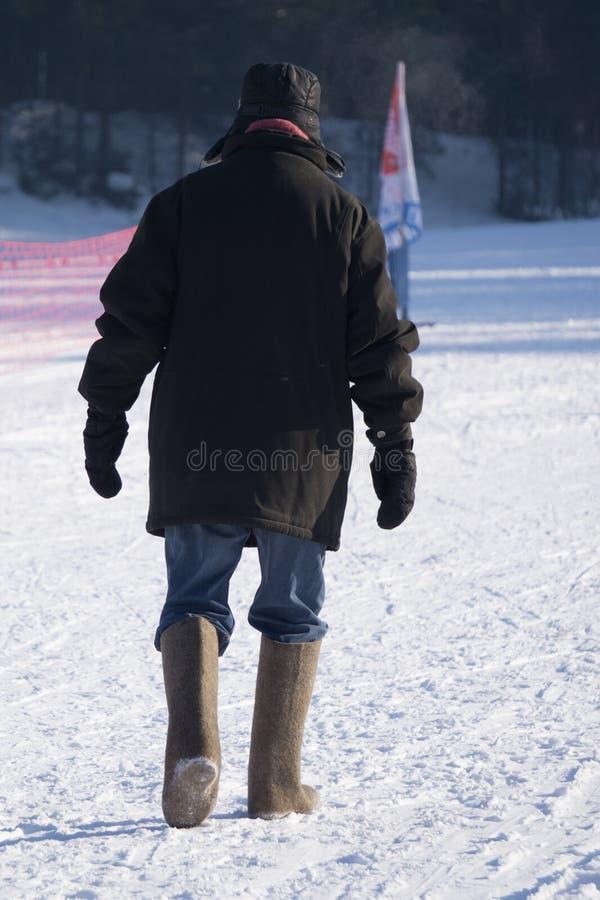 步行沿着向下在老革命衣物,减速火箭的样式冬天,俄罗斯的街道的两个人 库存照片