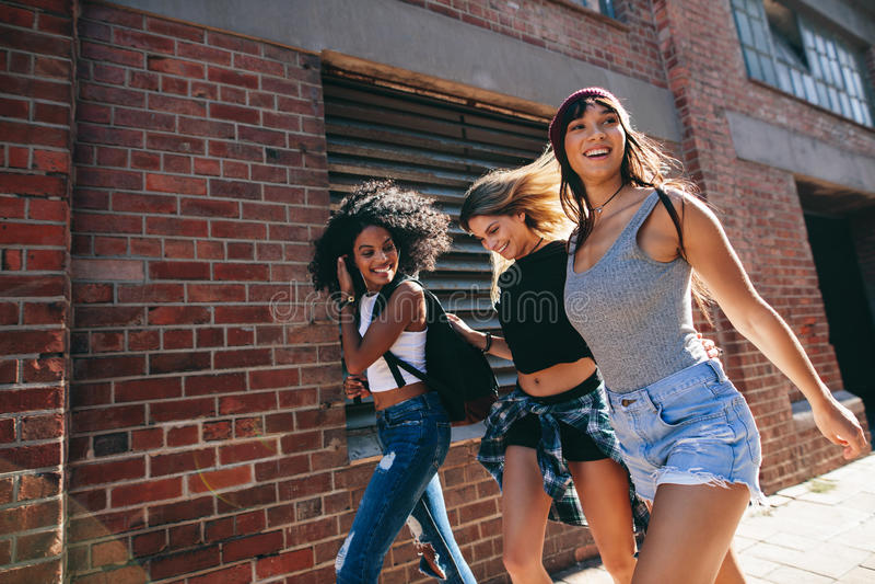 步行沿着向下城市街道的多种族小组朋友 免版税图库摄影