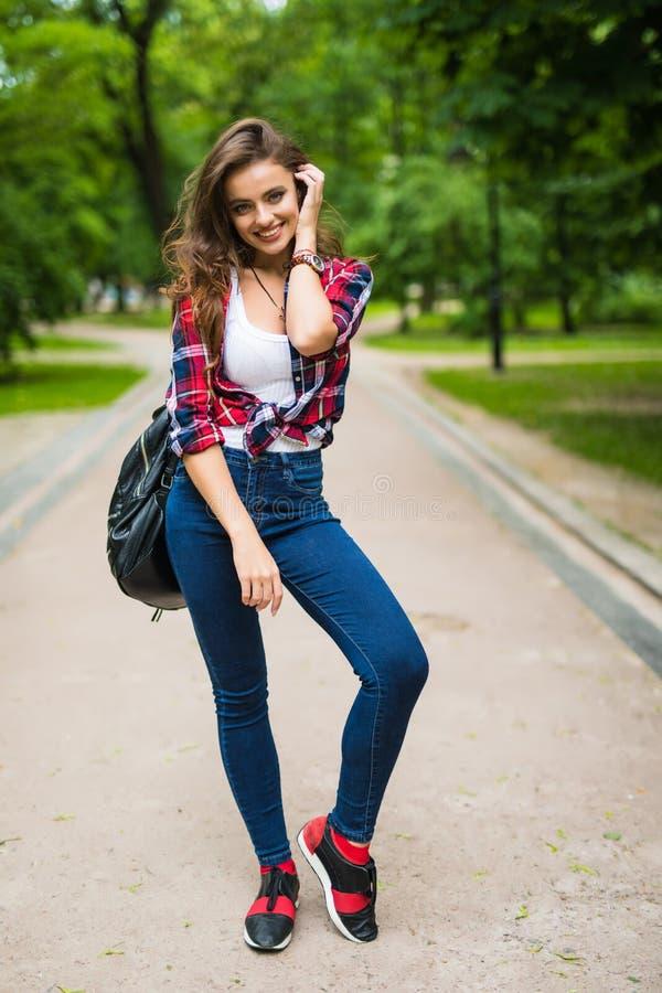 步行沿着向下有一个背包的街道的年轻学生女孩在公园 免版税库存图片