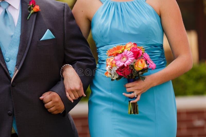 步行沿着向下有五颜六色的bo的走道的女傧相和男傧相 免版税图库摄影