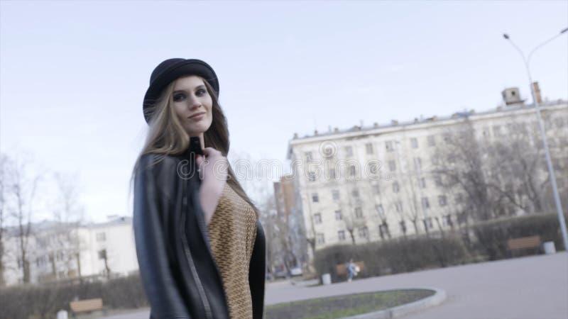 步行沿着向下有她的黑皮夹克的街道的女孩在她的振翼在的肩膀和长的直发 图库摄影