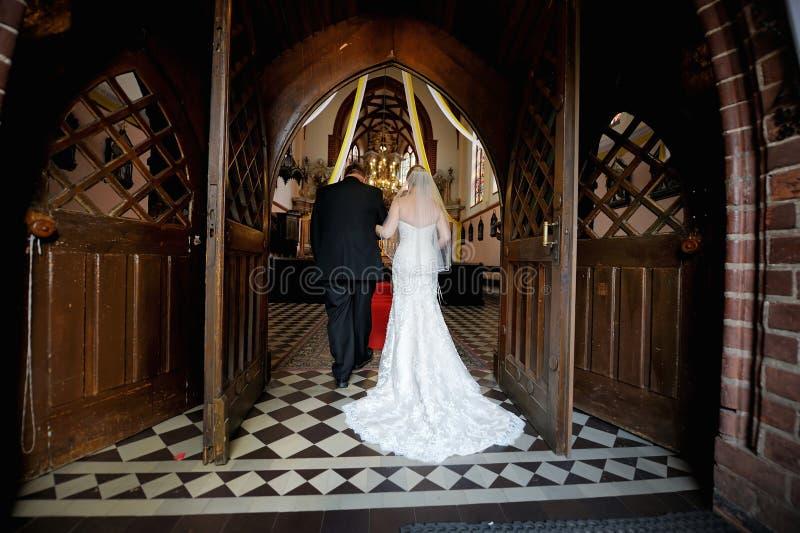 步行沿着向下有父亲的走道的新娘 库存照片