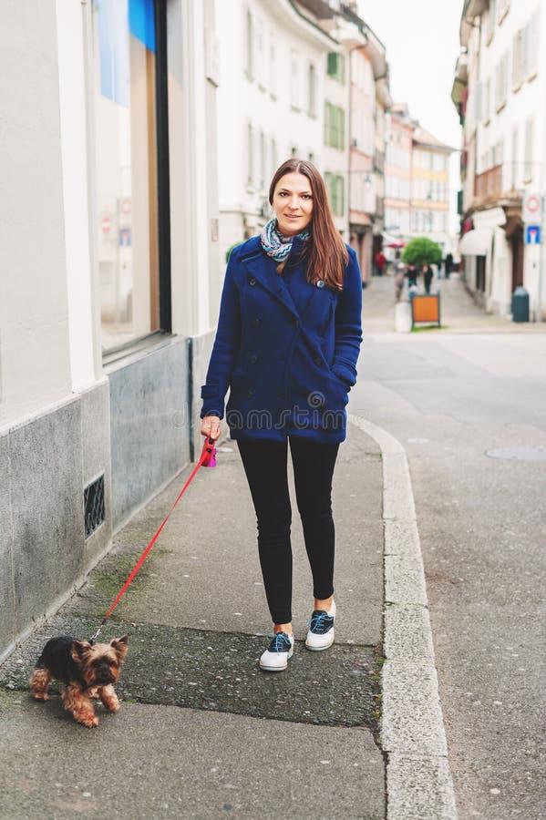 步行沿着向下有约克夏狗狗的街道的美丽的少妇 免版税图库摄影