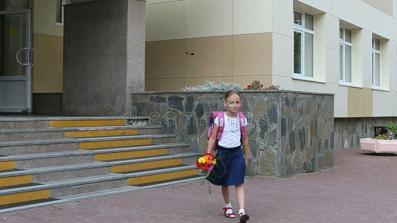 步行沿着向下有背包和花花束的台阶的女孩从学校门 回到概念学校 夏日hanheld 库存图片