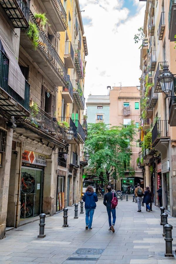 步行沿着向下狭窄的街道的人们在商店/商店之间在巴塞罗那 免版税库存图片