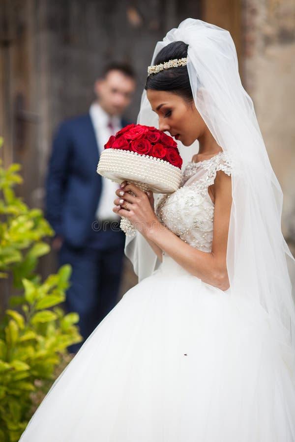 步行沿着向下老欧洲stree的典雅的美丽的深色的新娘 图库摄影