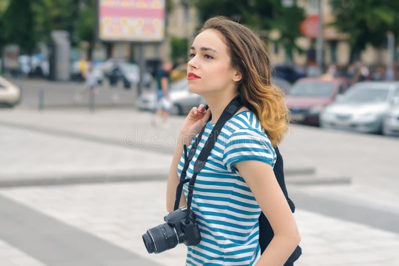 步行沿着向下街道的妇女摄影师 免版税库存图片