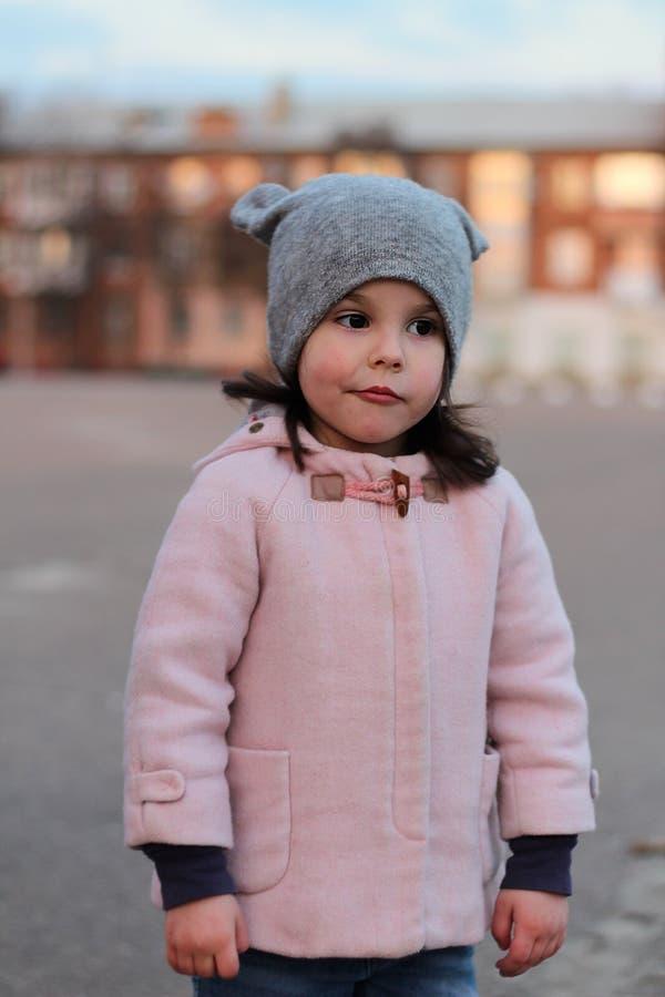 步行沿着向下街道的被触犯的小白女孩在晚上 在日落都市风景的背景的画象 库存图片