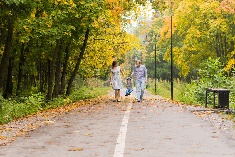 步行沿着向下路的愉快的年轻家庭外面在秋天自然 免版税库存照片