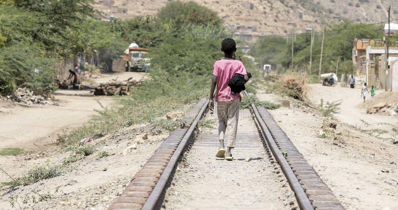 步行沿着向下铁轨的孩子在埃塞俄比亚的沙漠近 免版税库存照片