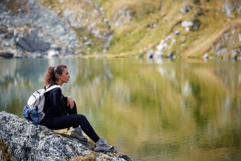 步行由山的湖的背包徒步旅行者夫人 免版税库存图片