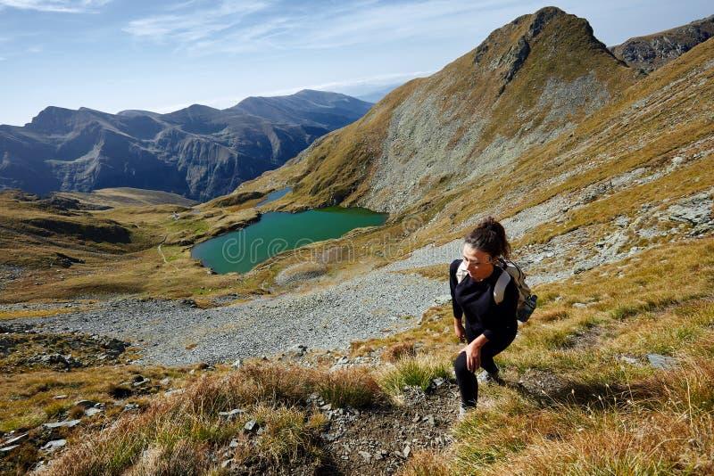 步行由山的湖的背包徒步旅行者夫人 免版税库存照片