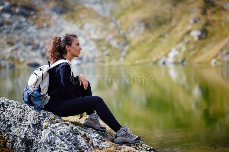 步行由山的湖的背包徒步旅行者夫人 图库摄影