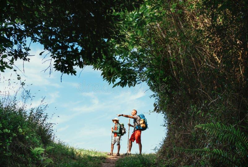 步行由森林路的父亲和儿子背包徒步旅行者,采取短的休息 旅行与孩子概念的愉快的父母 免版税库存照片