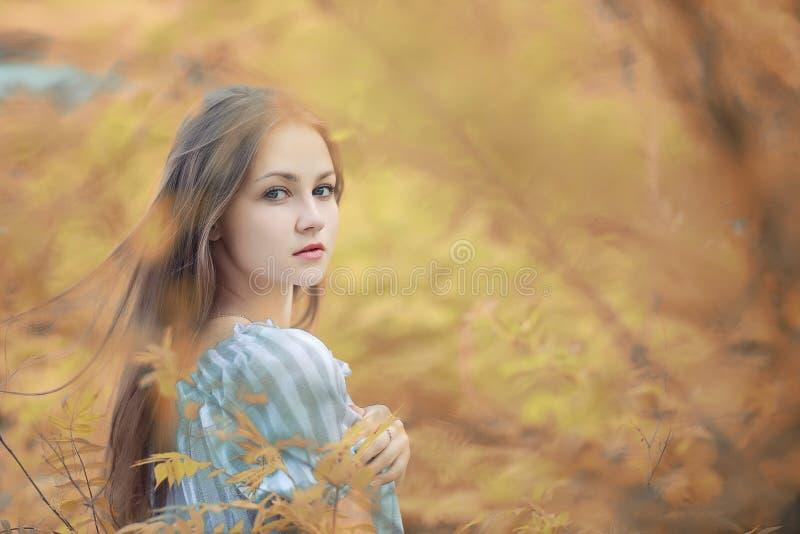 步行的女孩在秋天 免版税库存图片