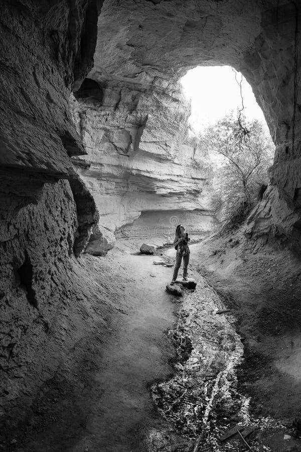 步行的年轻女人和探索地下洞城市在卡帕多细亚 免版税库存照片