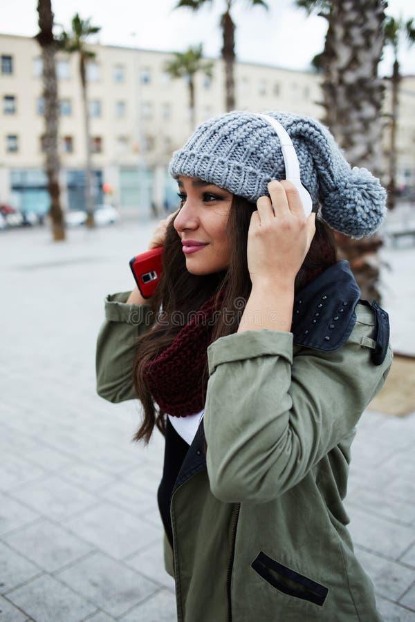 步行的美丽的女孩穿过城市 免版税库存图片