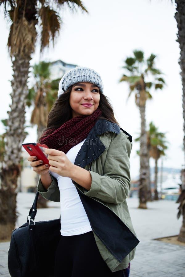 步行的美丽的女孩穿过城市 免版税库存照片