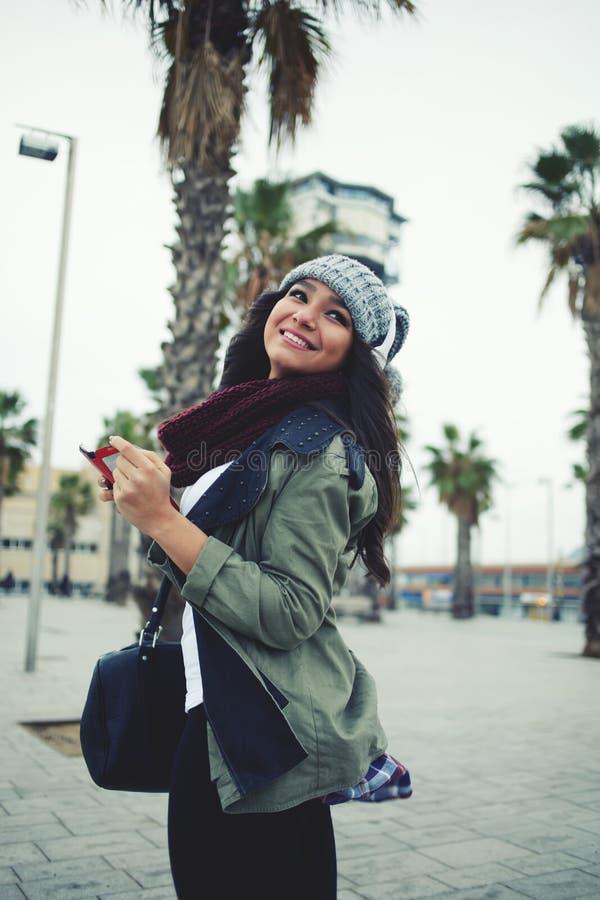 步行的美丽的女孩穿过城市 图库摄影