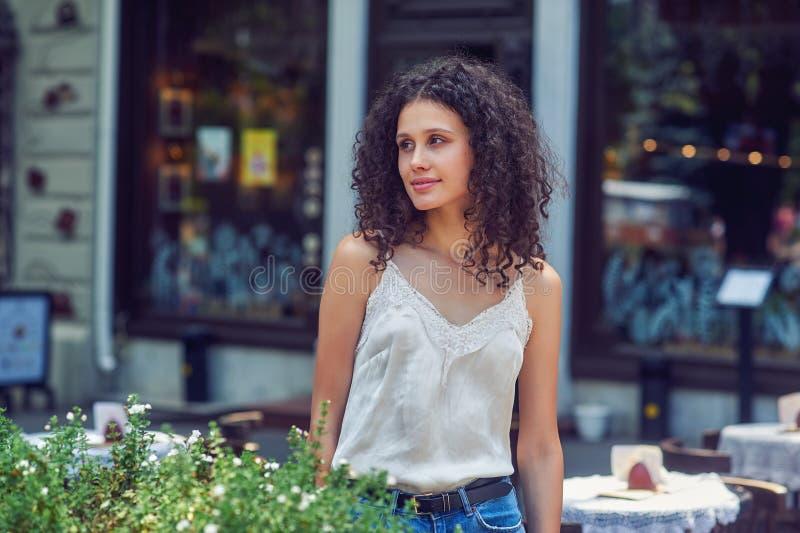 步行的美丽的少女在夏天城市 免版税库存图片