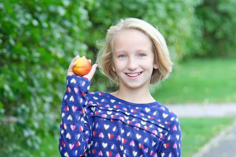 步行的美丽的白肤金发的孩子女孩在公园吃果子、油桃或者桃子 库存图片
