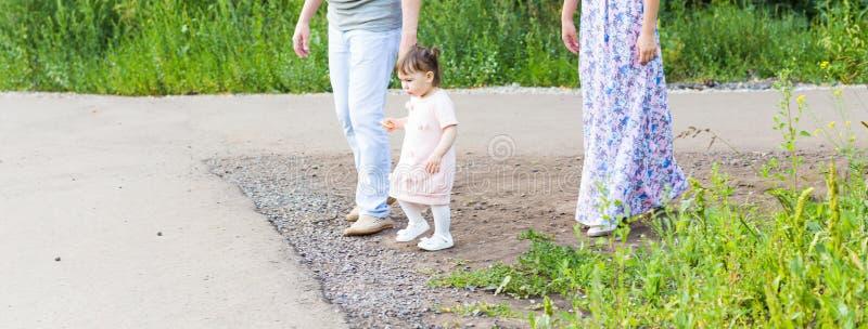 步行的逗人喜爱的矮小的亚裔女婴与父母 库存照片